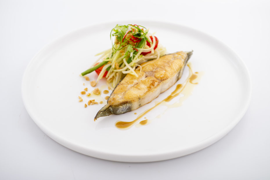 Golden pan-fried Nordic Halibut and som tam on a white dinner plate