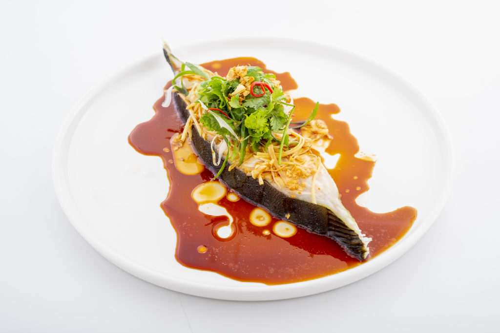 Steamed Nordic Halibut with hot soya sauce on a white plate