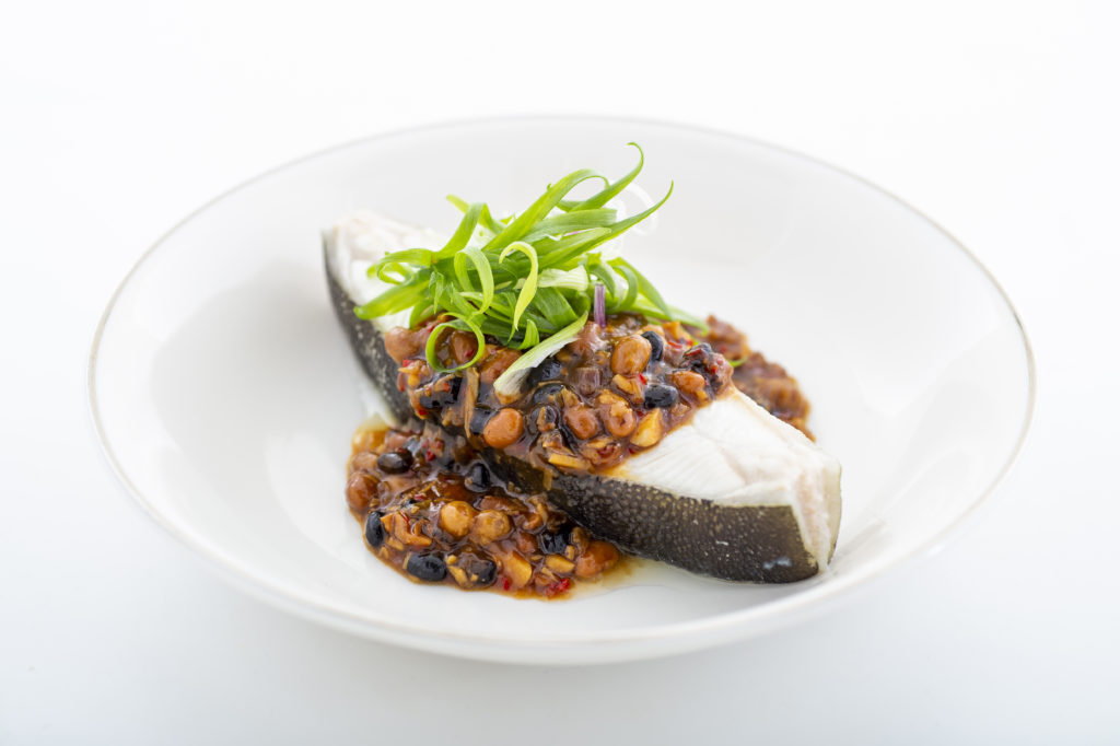 Steamed Nordic Halibut with black beans on a dinner plate